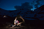 Charlie Bloch reads a book by headlamp at night in his tent at camp above Parika Lake, Never Summer Wilderness, Colorado.