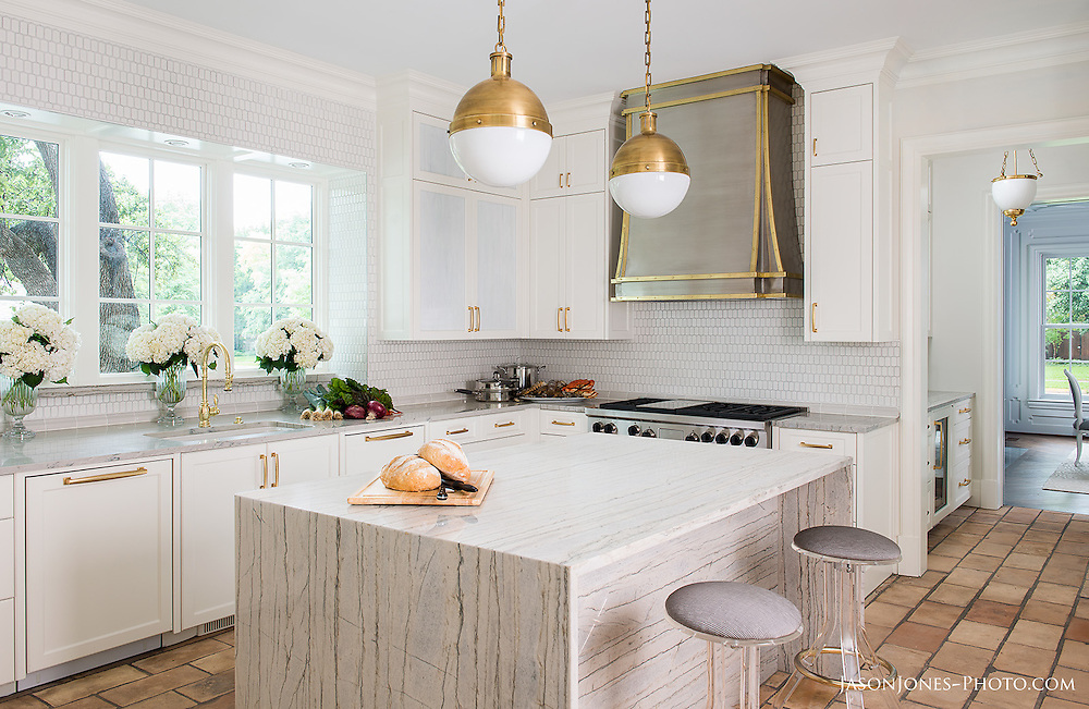 White marble kitchen with stainless appliances.