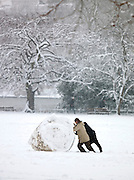 Two men rolling a giant snowball in St James Park, London, UK