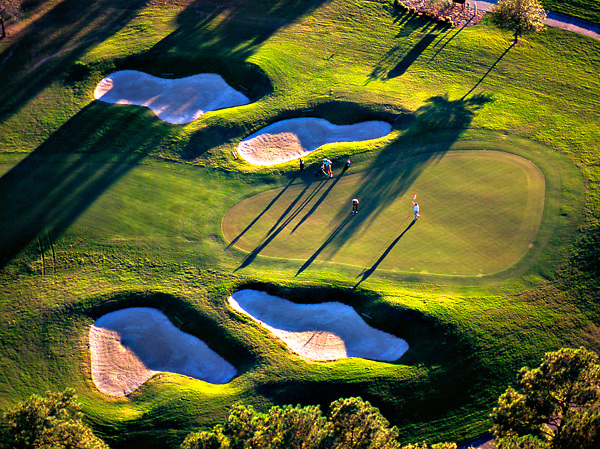Stock photo of an aerial view of a small group playing golf on the green