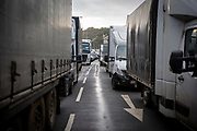 Trucks wait as tensions are high for drivers who have been waiting over 48 hours for the Port of Dover to re-open, on the 23rd of December 2020, Dover, Kent, United Kingdom. The French border was closed due to a new strain of COVID-19 all travellers are now waiting to receive a COVID-19 test before they can board a ferry to Calais, France. Dover is the nearest port to France with just 34 kilometres (21 miles) between them. It is one of the busiest ports in the world. As well as freight container ships it is also the main port for P&O and DFDS Seaways ferries.  (photo by Andrew Aitchison / In pictures via Getty Images)