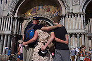 Tourists below the entrance to Basillica di San Marco in Piazza San Marco, Venice, Italy