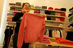 Jineen Abu Roqto, a sales clerk, adjust clothes inside the store where she works, Ramallah, Palestinian Territories, Feb. 13, 2005. Shops are open but not very busy inside the mall in Ramallah.