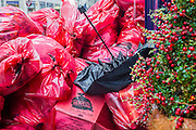 A new year's day parade passes through Piccadilly Circus on a wet and windy day. In the back streets the post Christmas and New year waste piles up and homless people are ignored by visitors loaded down by bags. London, UK 01 Jan 2014. Guy Bell, 07771 786236, guy@gbphotos.com