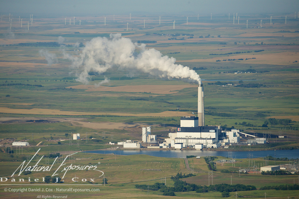 A Minnkota coal fired power plant on the prairies of North Dakota belching steam and carbons contrast directly with the line of more modern, electricity generating windmills in the far distance.