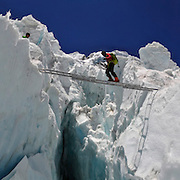 Panorama of Brent Bishop crossing a ladder over a massive crevasse in the Khumbu Icefall on Mount Everest, Nepal.<br />