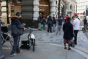 As the UKs Coronavirus death toll during the governments social distancing lockdown, rose by 384 to 33,998, and the R rate of infection is reported to be between 0.7 and 1.0, customers and Uber Eats riders wait for their orders outside a Five Guys restaurant who are open only for take-aways and deliveries, in accordance with government lockdown guidelines, on 15th May 2020, in London, England.