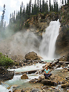 A woman enjoys sitting at the base of Laughing Falls on a beautiful summer day; Yoho National Park, near Golden, British Columbia, Canada