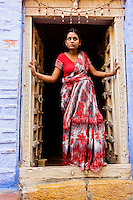 Portrait of a woman in a red saree standing in a doorway, Jodhpur, India. Exotic people and places wall art. Fine art photography prints for sale.