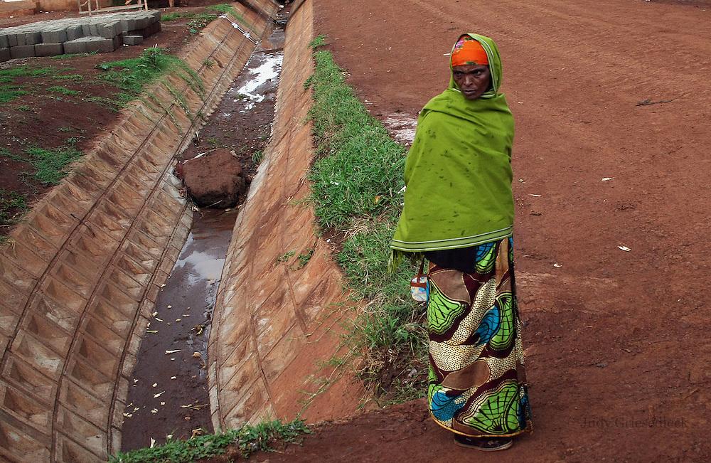A Tanzanian woman along the side of a drainage ditch in Arusha, Tanzania.