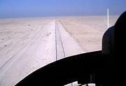 Oil industry Saudi Arabia, helicopter Bell 206 JetRanger 1979 pilot in cockpit view of desert railway