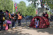 24 hours before the royal marriage of Prince William and Kate Middleton, schoolchildren watch a marching band pass-by while in a tent, a family of royalists peer out. Taking place on Friday 30th April in front of millions of Britons and foreign tourists (many American), the crowds are already gathering to claim their ideal locations in the front rows along the procession route.