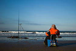 © Licensed to London News Pictures. <br /> 12/10/2014. <br /> <br /> Saltburn, United Kingdom<br /> <br /> A fisherman takes a seat as he takes part in the annual Jim Maidens memorial beach fishing competition in Saltburn by the Sea in Cleveland. <br /> The competition is held each year to mark the death of Saltburn plumber and keen fisherman Jim Maidens who died in 1998 when he was killed after being swept overboard from his boat 'Corina' close to the beach at Saltburn.<br /> <br /> Photo credit : Ian Forsyth/LNP