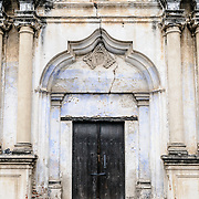 A doorway onto the street from the monastery and church of Santa Clara (Saint Clair) in Antigua, Guatemala. The original foundation dates back to 1700 and the church was consecrated in 1715. It was run by nuns from the Second Franciscan Order of Poor Sisters of Saint Clair. In 1717 the earthquake of San Miguel caused extensive damages to the building. The church is now in ruins and is no longer a functional church.