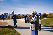 "18 OCTOBER 2020 - DES MOINES, IOWA: People use noisemakers during ""Shattering the Silence"" on the grounds of the Iowa Judicial Branch, with the Des Moines city skyline in the background. About 100 people gathered on the grounds of the Iowa Judicial Building in Des Moines to ""shatter the silence"" on racism. The event, Shattering the Silence, was designed to call on white people and especially white people of faith to do racial justice work and to no longer remain silent about racial justice and police violence against people of color.          PHOTO BY JACK KURTZ"