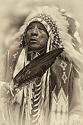 Ute Native American Chief in full regalia at a regional Pow-Wow. The Chief if also carrying an eagle feather fan.