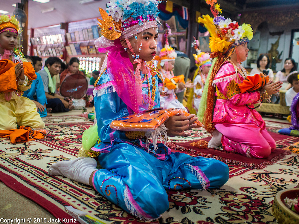 """06 APRIL 2015 - CHIANG MAI, CHIANG MAI, THAILAND:  Boys being ordained novice monks pray during their ordination on the last day of the three day long Poi Song Long Festival in Chiang Mai. The Poi Sang Long Festival (also called Poy Sang Long) is an ordination ceremony for Tai (also and commonly called Shan, though they prefer Tai) boys in the Shan State of Myanmar (Burma) and in Shan communities in western Thailand. Most Tai boys go into the monastery as novice monks at some point between the ages of seven and fourteen. This year seven boys were ordained at the Poi Sang Long ceremony at Wat Pa Pao in Chiang Mai. Poy Song Long is Tai (Shan) for """"Festival of the Jewel (or Crystal) Sons.  PHOTO BY JACK KURTZ"""