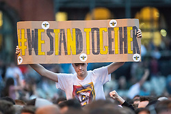 """© Licensed to London News Pictures . 27/05/2017 . Manchester , UK . A man holds up a hand painted sign , with Manchester bee stickers , reading """" WE STAND TOGETHER """" during the Courteeners' set . Manchester music line up , featuring Courteeners , Charlatans , Blossoms and Cabbage , at the Emirates Old Trafford Stadium . Photo credit : Joel Goodman/LNP"""