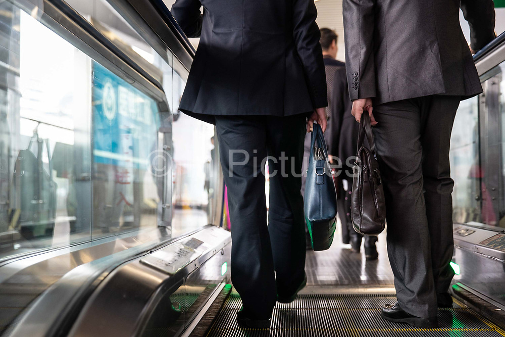 Two men traveling up an escalator while holding brief cases at a CRT Chongqing Rapid Transit station in Chongqing, China, on Thursday, April 14, 2016. The municipality of 30 million people saw state-led development approach fueled the fastest pace nationwide, with President Xi Jinping praising policy innovations that have included subsidized housing and relaxed residency rules that encourage labor mobility.