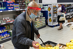 Profoundly deaf and elderly man shopping in Lidl supermarket wearing face mask and visor during Coronavirus lockdown, Reading UK May 2020. Verbal model release