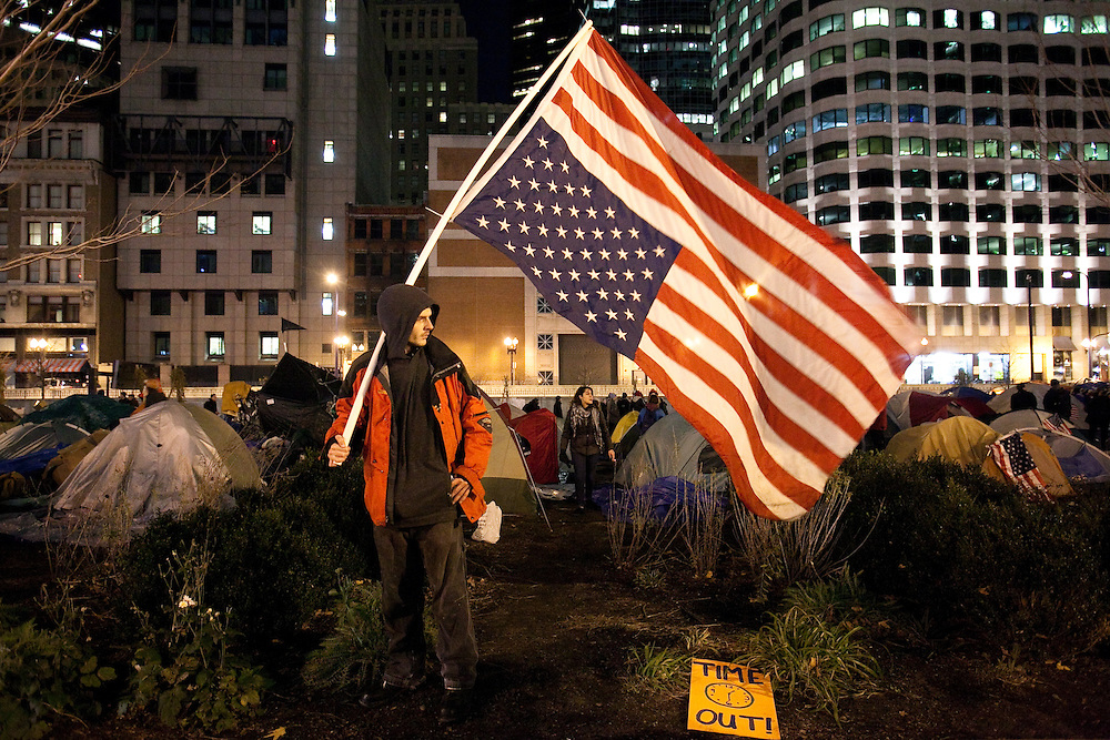"""Boston, MA 12/08/2011.Garret Kirkland of Winchester carries an American flag upside down as a symbol of distress at the Occupy Boston campsite on Thursday evening.  Said Kirkland, """"This is a country in distress.  We've thrown the constitution out the window."""""""