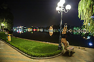 A man does acrobatic exercises on a bench beside Hoan Kiem Lake in Hanoi, Vietnam, Southeast Asia