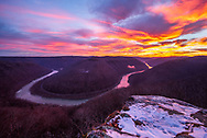 The morning sunrise sets a colorful sky against the late wintery back drop at Grandview State Park overlooking the New River in West Virginia.