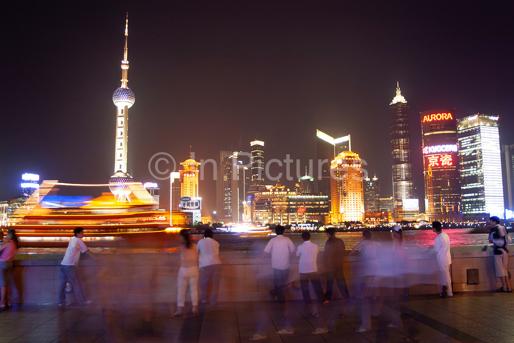 Tourists on the Bund at sunset look out over the cityscape and skyline of Pudong Financial District over Huang Pu River in Shanghai, China. Every day at sundown, tourists gather to watch the sun go down and the lights all along the Huang Pu River come to life.