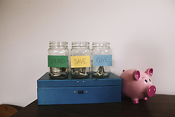 August 8, 2017 - Close up of blue metal box, three glass jars with money and handwritten labels and a pink piggy bank. (Credit Image: © Mint Images via ZUMA Wire)