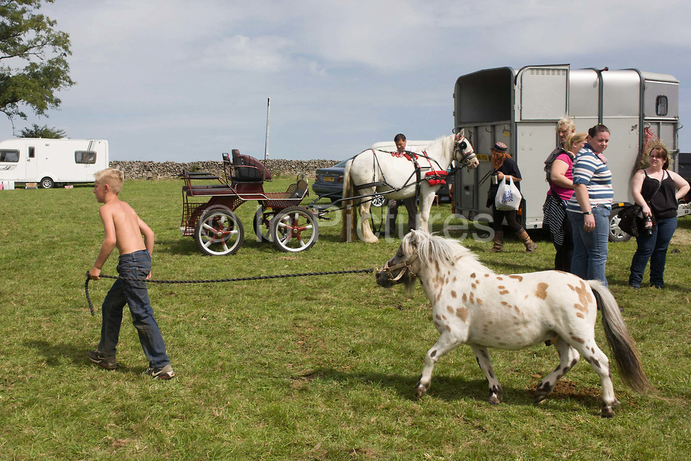 A young traveller tries out a Shetland pony at the ancient annual Priddy Sheep (and horse) fair in Somerset, England. Leading round the horse on a rope, the traveller boy parades around a field on the outskirts of the village. Set in the Mendip Hills, in the south-western English county of Somerset, the Priddy Sheep fair is host to an odd mix of farmers and travellers (commonly and incorrectly known as gypsies). In this field set aside purely for travellers, many with West Country accents but also with nearby Welsh and Irish too, deals are done with a traditional spit on the hand and a smacking of palms, selling a pony to another family. The Priddy Sheep Fair moved from the city of Wells in 1348 because of the Black Death.