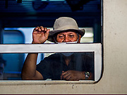 11 APRIL 2018 - BANGKOK, THAILAND:  A man looks out the window of his train carriage in Hua Lamphong train station in Bangkok on the first day of the Songkran travel period. Songkran is the traditional Thai New Year and is one of the busiest travel periods of the year as Thais leave the capital and go back to their home provinces or resorts in tourist areas. Trains and busses are typically jammed the day before the three day Songkran holiday starts. The government has extended the official holiday period through Monday, 16 April because one day of the Songkran holiday fell on the weekend, giving many workers a five day holiday.     PHOTO BY JACK KURTZ