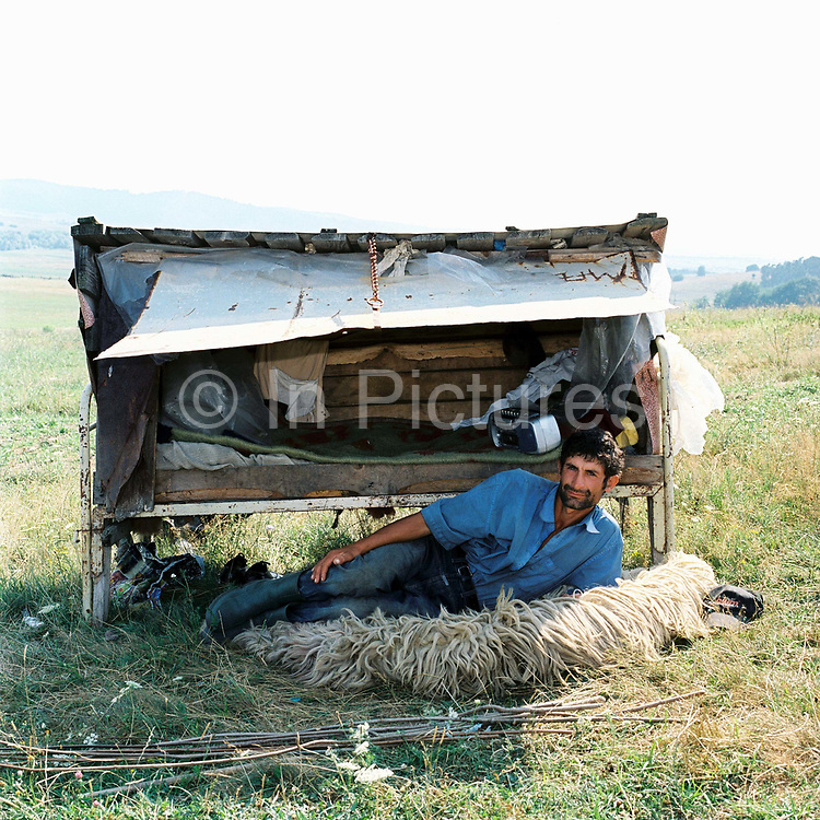 A shepherd lies on a fleece in front of his 'busca'. In the lower valleys in Saxon Transylvania shepherds often sleep in 'busca', individual portable sleeping compartments whilst looking after the sheep in the summer months.