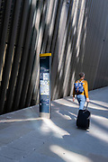 A man wearing a rusksack pulls a small suitcase behind him while walking past corporate architecture where a map of the City of London is positioned, in the capital's financial district, on 24th September 2021, in London, England.