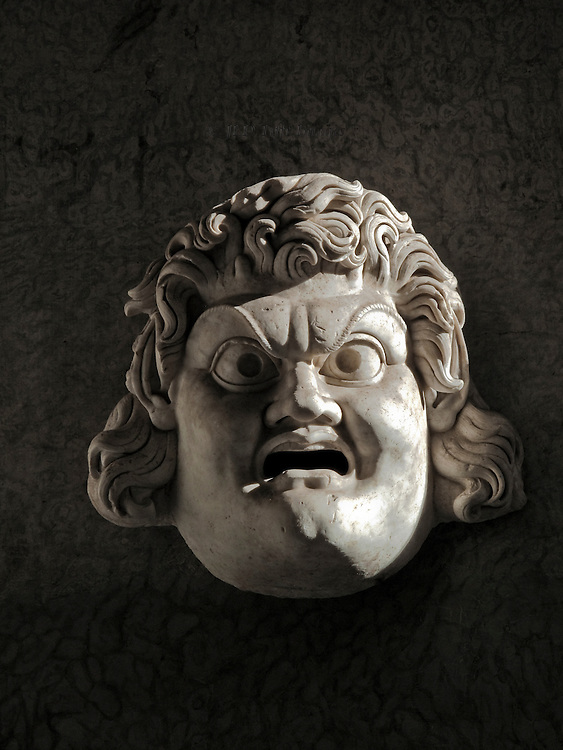 Close up of a ferocious looking Hellenistic theatrical mask on display at the Vatican Museums.  Its eyeballs are painted in, mouth open, head covered with curly hair.