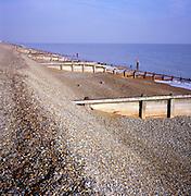 Wooden groynes on shingle beach as coastal defence controlling longshore drift, Slaughden, Aldeburgh, Suffolk, England