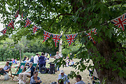 Union Jack bunting hangs over a British summer fete bringing the local community together and to celebrate their important public space, on 24th June 2017, in Ruskin Park, the south London borough of Lambeth, England. Bunting is a festive decoration made of fabric, or of plastic, paper or even cardboard in imitation of fabric. Typical forms of bunting are strings of colorful triangular flags and lengths of fabric in the colors of national flags gathered and draped into swags or pleated into fan shapes. The term is also used to refer to a collection of flags, and particularly those of a ship. The officer responsible for raising signals using flags is known as bunts, a term still used for a ships communications officer.