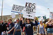 Students hold signs in protest over the ongoing school shootings that continue plaging the US at Dallas Cityt Hall on Saturday.