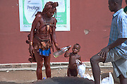 """A traditionally dressed Himba woman with her child outside a supermarket in Opuwo, a town well known for cultural tourism in northwestern Namibia, after receiving money from a tourist in exchange for a photograph.  Like most traditional Himba women, she covers herself from head to toe with an ochre powder and cow butter blend. Some Himba are turning to tourism to kick-start their entry into the cash economy, setting up demonstration villages advertising """"The Real Himba."""""""