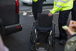 London, UK. 13 October, 2019. Police officers put a wheelchair belonging to a disabled climate activist from Extinction Rebellion arrested using Section 14 of the Public Order Act 1986 into a police vehicle during a protest outside New Scotland Yard against tactics employed by police officers which impinge on the right to protest of disabled activists, including the confiscation of wheelchairs, wheelchair ramps, accessible toilets and tents.