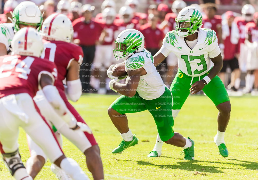 PALO ALTO, CA - OCTOBER 2:  CJ Verdell #7 takes a handoff from Anthony Brown #13 of the Oregon Ducks during an NCAA Pac-12 college football game against the Stanford Cardinal on October 2, 2021 at Stanford Stadium in Palo Alto, California.  (Photo by David Madison/Getty Images)