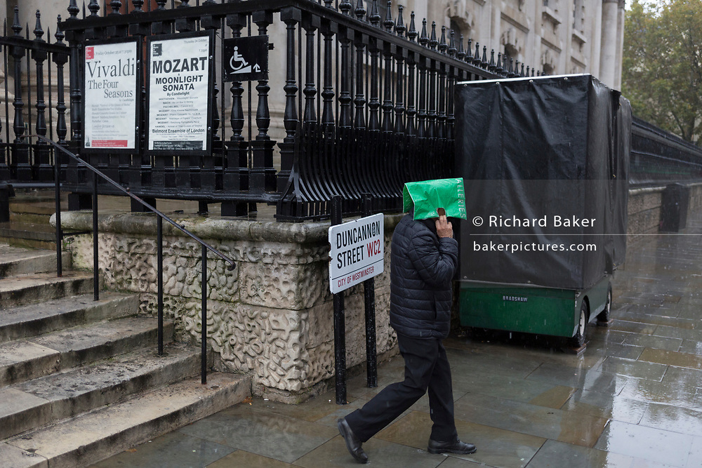 A Londoner covers his head during heavy rainfall on an autumn afternoon outside St. Martin-in-the-Fields church on Trafalgar Square, on 24th October 2019, in Westminster, London, England.