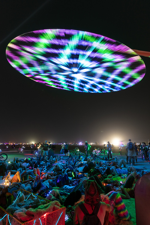 Paraluna by: Christopher Schardt from: Oakland, CA year: 2018<br /> <br /> Paraluna combines kinetic sculpture, LEDs and music. Its main component is a disc 10m in diameter with 17,280 LEDs. A computer controls the LEDs while rotating, raising, lowering, and tilting the disc.<br /> <br /> Some of the LED patterns work with the rotation of the disk, creating spirals. Others use persistence-of-vision, making an image hover in space above the spinning LEDs. Spokes demonstrates both of these styles: https://photos.app.goo.gl/DcP9IauNTjRHENUh2<br /> <br /> Surrounding the disc are several high-quality speakers that play classical music at comfortable, yet immersive volume, creating a comfortable, peaceful place to be. Patterns are chosen to complement each musical piece, as with Firmament:<br /> https://photos.app.goo.gl/H6KCzkf5jkGWAA3m2 My Burning Man 2018 Photos:<br /> https://Duncan.co/Burning-Man-2018<br /> <br /> My Burning Man 2017 Photos:<br /> https://Duncan.co/Burning-Man-2017<br /> <br /> My Burning Man 2016 Photos:<br /> https://Duncan.co/Burning-Man-2016<br /> <br /> My Burning Man 2015 Photos:<br /> https://Duncan.co/Burning-Man-2015<br /> <br /> My Burning Man 2014 Photos:<br /> https://Duncan.co/Burning-Man-2014<br /> <br /> My Burning Man 2013 Photos:<br /> https://Duncan.co/Burning-Man-2013<br /> <br /> My Burning Man 2012 Photos:<br /> https://Duncan.co/Burning-Man-2012
