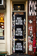 """A doorfront in New York City's East Village with sticks containing the phrase """"Does It Even Matter"""""""