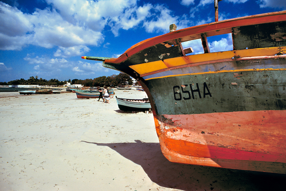 Brightly painted fishing boats lie on the white sandy beach at Nabuel, Tunisia.