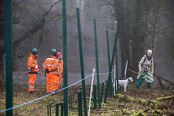 Denham, UK. 6 February, 2020. An environmental activist observes engineers working on behalf of HS2 constructing a security fence at Denham Ford. Works planned for the HS2 high-speed rail link in the immediate vicinity include the construction of a Bailey bridge across the ford and a compound in Denham Country Park requiring the felling of mature trees. Some of the site lies within a wetland nature reserve forming part of a Site of Metropolitan Importance for Nature Conservation (SMI).