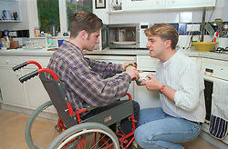 Carer assisting young wheelchair user to prepare meal in kitchen,