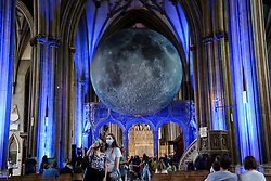 © Licensed to London News Pictures. 15/08/2021. Bristol, UK. Women take a selfie with Luke Jeram's Moon installation in Bristol Cathedral. Measuring seven metres in diameter, the Museum of the Moon features detailed NASA imagery of the lunar surface. At an approximate scale of 1:500,000 each centimetre of the internally lit spherical sculpture represents 5 km of the moon's surface. The Museum of the Moon  is open until 30 August 2021. Photo credit: Dinendra Haria/LNP