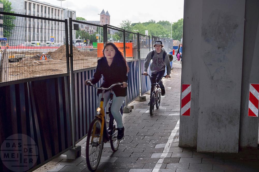 Fietsers rijden over een heel smal tweerichtingenfietspad tussen een hek en een betonpaal in het stationsgebied van Utrecht, waar veel werkzaamheden plaatsvinden. <br /> <br /> Cyclists ride on a very narrow two-way cycle path between a fence and a concrete pile in the station area of Utrecht, where many activities take place.