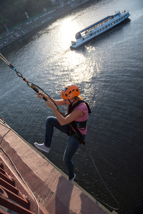 After jumping off the Parkovy Pedestrian Bridge attached to a rope and swinging above the Dnieper River, a Ukrainian woman returns to the top of the bridge. Kiev, Ukraine