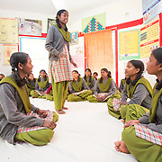 CAPTION: Mahila Samakhya students act out a role-play. In the play, the old lady's granddaughter has just started menstruating. She is worrying about what's happening her, so goes to her grandmother and asks why this is suddenly happening to her. The old lady reassures her that it happens to every woman; that it also happened to her, and that there's nothing to worry about, everything will be alright. The girl who then comes along is playing the role of a sahiya. She is visiting the household, and reassures the girl that it's a natural process for all young girls, and goes on to explain how to take care of nutritional intake including supplementation during this period, and also how to be clean and hygienic. She then assures her that if she experiences very bad pain, she can come to her for some medicines. LOCATION: Mahila Samakhya, Ratu (block), Ranchi (city), Jharkhand (state), India. INDIVIDUAL(S) PHOTOGRAPHED: Foreground, from left to right: Shobha Pareya, Sita Kujur, Ganga Purti and Salomi Horo; background: multiple people.